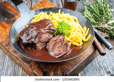 Traditional German braised beef cheeks in brown red wine sauce with spaetzle herbs as closeup in a wrought-iron skillet on a wooden board
