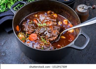 Traditionell gebackene Wangen aus deutschem Rindfleisch in brauner Rotweinsauce mit Karotten und Zwions, die in einem holländischen Ofen aus Gusseisen auf einem alten rustikalen Karton als Nahaufnahme angeboten werden