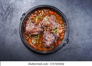 Traditionell gebackene Rind-Wangen aus Braun-Rotweinsauce mit Karotten und Zwiebeln, die als Top-Aussicht in einem modernen Design-Stewpot auf einem alten rustikalen Karton angeboten werden