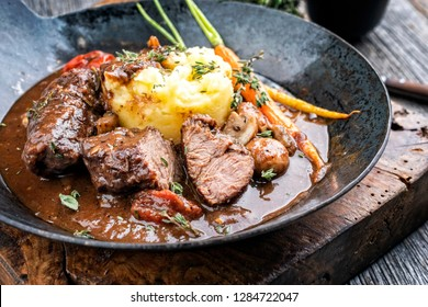 Traditional German braised pork cheeks in brown sauce with mushroom and mashed potatoes as closeup wrought-iron pan