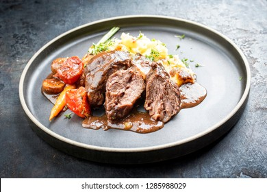 Traditional German braised pork cheeks in brown sauce with mushroom and mashed potatoes as closeup on a modern design plate