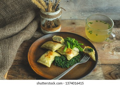 traditional German cuisine, delicious, baked Maultaschen with spinach sauce and green legumes, next to it stands a glass of hot broth of beef