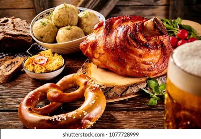 Traditional German cuisine, Schweinshaxe roasted ham hock, pretzel, obatzter cheese spread with glass of pale beer on wooden table