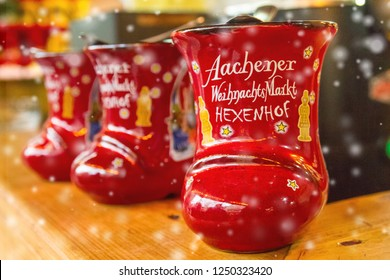 Traditional german holiday alcoholic drink - punch (Feuerzangenbowle) in cup in the form of shoe with German text, translated as - Aachen Christmas Market, Aachen, Germany