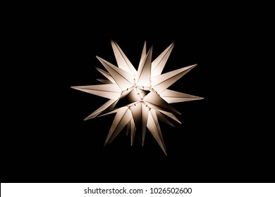 Traditional German Moravian Christmas star light on black background.