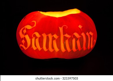 Traditional glowing Samhain Jack-o-Lantern with carved word 'Samhain' on it. Pagan Wiccan Wheel of the Year holiday celebration.