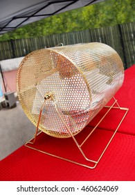 A traditional gold raffle drum full of contest entry ballots on a table top at an outdoor event.