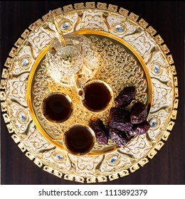 Traditional golden arabic coffee set with dallah, three cups of tea and dates. Dark background. Square image. Top view.