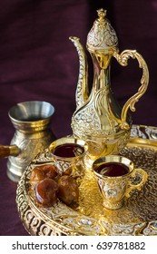 Traditional golden Arabic coffee set with dallah, coffee pot and dates. Dark background. Vertical photo.