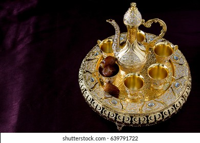 Traditional golden arabic coffee set with dallah, two cups and dates. Dark background. Horizontal photo