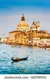 Traditional Gondola on Canal Grande with Basilica di Santa Maria della Salute in the background at sunset, Venice, Italy