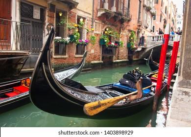 Traditional gondola in venetian water canal in Venice, Italy. Scenic gondola in Venezia in narrow street