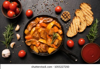 Traditional goulash stewed meat with potatoes, carrots and vegetables in a cast-iron frying pan on a wooden background with croutons, rosemary, garlic and tomatoes. Flat lay. Top view.