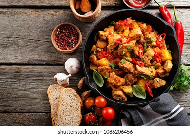 Traditional goulash stewed meat with potatoes, carrots and vegetables in a cast-iron frying pan on a dark wooden background. top view.