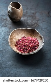 Traditional gourmet red wine salt as closeup in a earthenware bowl with copy space