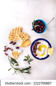 Traditional Greek Appetizer Dzadziki or Tzatziki served with corn pita bread with organic kalamata olives, decorated with Olive oil and olive tree branch. Top View