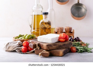Traditional greek appetizer goat feta cheese served with fresh cherry tomatoes, herbs, green and black olives and extra virgin olive oil over a grey background.