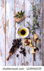 Traditional Greek Appetizer olives with bread and olive oil served on rustic olive wooden board over a white wooden background. Top View