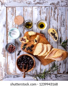 Traditional Greek Appetizer olives with bread,  olive oil and balsamic vinegar served on rustic olive wooden board over a white wooden background. Top View