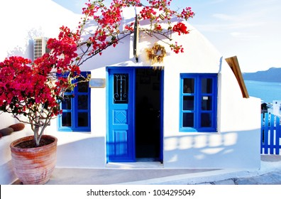 Traditional Greek architecture and pink flowers, Santorini Island, Greece. Beautiful details of Santorini island, white houses, blue doors and shutters, pink flowers, blue sky.