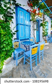 Traditional greek blue blinds and chairs on a small back street