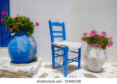 Traditional greek blue chair together with flower pots
