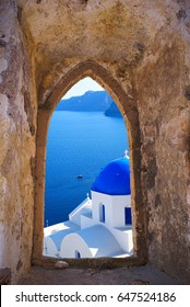 Traditional greek church  through an old window in Santorini island, Greece