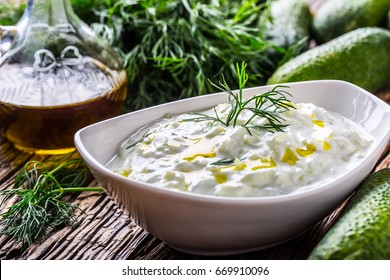 Traditional greek dip sauce or dressing tzatziki prepared  with grated cucumber sour cream yogurt olive oil and fresh dill.