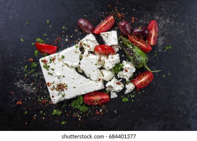 Traditional Greek Feta with Vegetable as top view on an old rusty metal sheet