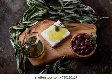 Traditional Greek mezze olives and feta decorated with branches of olive tree served with a jar of olive oil on an olive boad over a rustic metal background. Top View