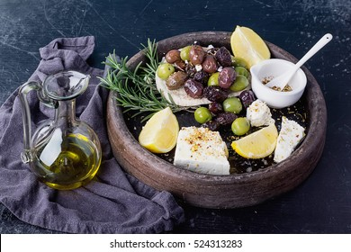 Traditional Greek and Middle east appetizer, various olives  and Feta cheese served with fresh pita bread, herbs,  seasoning and lemon in vintage ceramic plate over a rustic black board background.