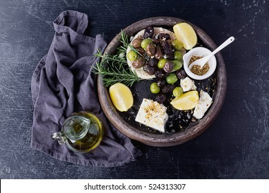 Traditional Greek and Middle east appetizer olives  and Feta cheese served with fresh pita bread, herbs,  seasoning and lemon in vintage ceramic plate over a rustic black board background. Top View