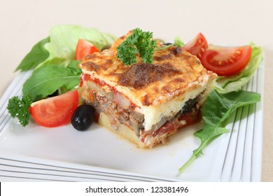 A traditional Greek moussaka, made with layers of potato, aubergine, meat, and tomato sauce, topped with bechamel sauce and served with salad.