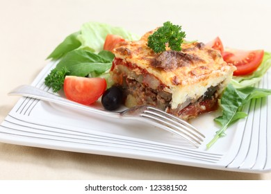 A traditional Greek moussaka on a plate with a fork, made with layers of potato, aubergine, meat, and tomato sauce, topped with bechamel sauce and served with salad.