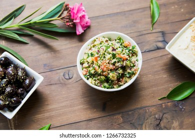 Traditional Greek salad with couscous and vegetables served on the wooden table with olives and flower beside