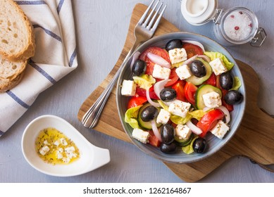 Traditional greek salad with feta cheese and olives on grey background