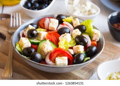 Traditional greek salad with feta cheese and olives on white wood