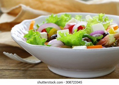 Traditional Greek salad with feta cheese, tomatoes, olives and green lettuce
