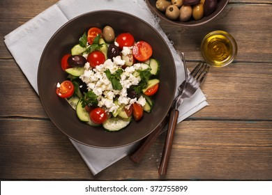 Traditional greek salad with fresh vegetables, feta cheese and olives. Top view. Rustic style. Selective focus