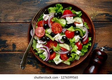 Traditional greek salad with vegetables and feta cheese in a clay bowl over dark wooden background.Top view with copy space.