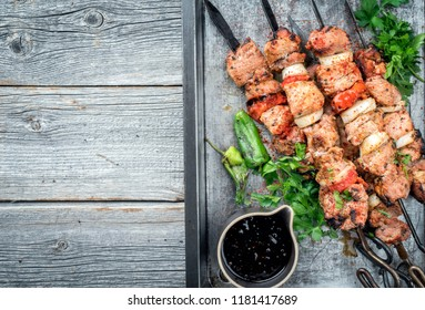 Traditional Greek souvlaki barbecue skewer with tomato, onion and paprika as closeup on a metal griddle with copy space left