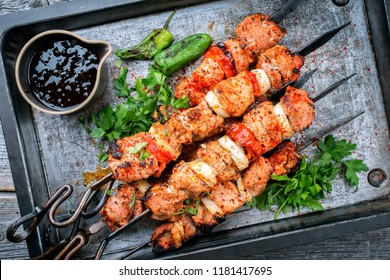 Traditional Greek souvlaki barbecue skewer with tomato, onion and paprika as closeup on a metal griddle