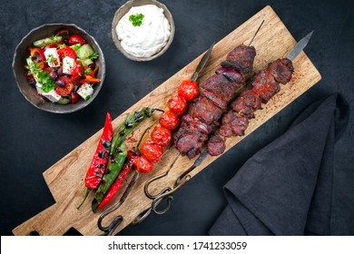 Traditioneller griechischer Souvlaki-Grillspieß mit Bauernsalat und Tzatziki als Top-Aussicht auf ein Holzschnitbrett