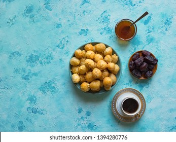 Traditional Greek sweets Loukoumades from dough with honey syrup with coffee and dates.