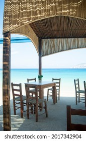 Traditional Greek taverna, Koufonisi island, Greece Simple seaside restaurant by the beach. Vertical shot.  No people.  Blurred background with copy space.