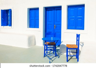 Traditional greek white architecture with blue doors and windows. Blue table with two chairs on the patio. Santorini island, Greece.