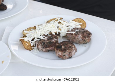 Traditional grilled Balkan meatballs served with pommes frites and Bulgarian white cheese