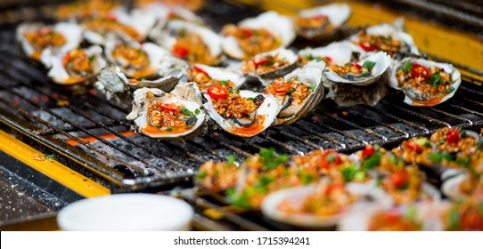 Traditional grilled seafood snacks on the Chinese street, arranged with conch and oyster on the grill, Xiamen, Chin