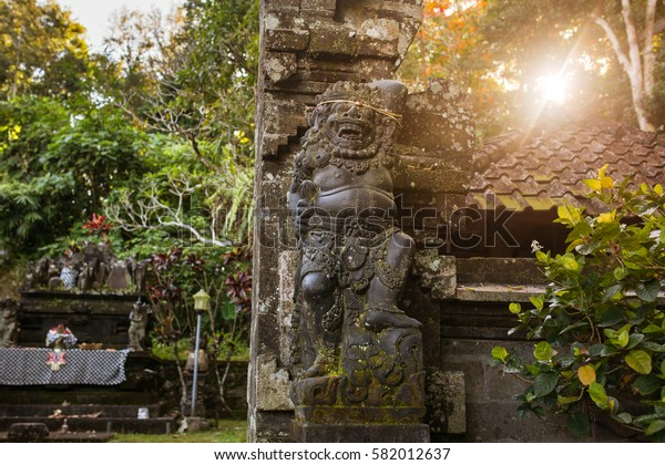 Traditional guard demon statue carved in dark stone on Bali island, Indonesia