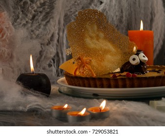 Traditional Halloween food - pumpkin pie with spiders, cobweb and candles, terribly delicious food for Halloween